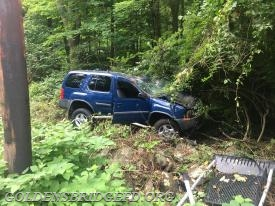 The vehicle involved in the accident, shown in the woods.