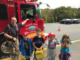 GOLDEN RULES OF FIRE SAFETY … Increase Miller Elementary School second-grade students (l.-r.) John Klein, Wesley Cotrone, Sophie Byrne and Cailin Grskovic learned the golden rules of fire safety from Ray Baker, Jr., Rescue Lieutenant of the Golden's Bridge Fire Department, when he and other members of the Department recently spent an entire day at the school providing interactive demonstrations and presentations as part of National Fire Prevention Week. Students were rewarded for their attentiveness and participation in this important exercise, as the members of the Department provided each with a drawstring backpack filled with fire safety and prevention reminders, including an activity book, ruler, pencil, shiny red fire hat and other items.