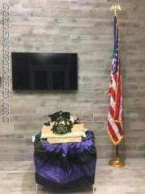 His gear is set up in the firehouse lobby with memorial bunting underneath it.